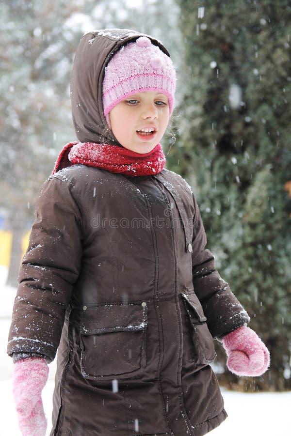 冬天布料的女孩享用雪的 免版税图库摄影