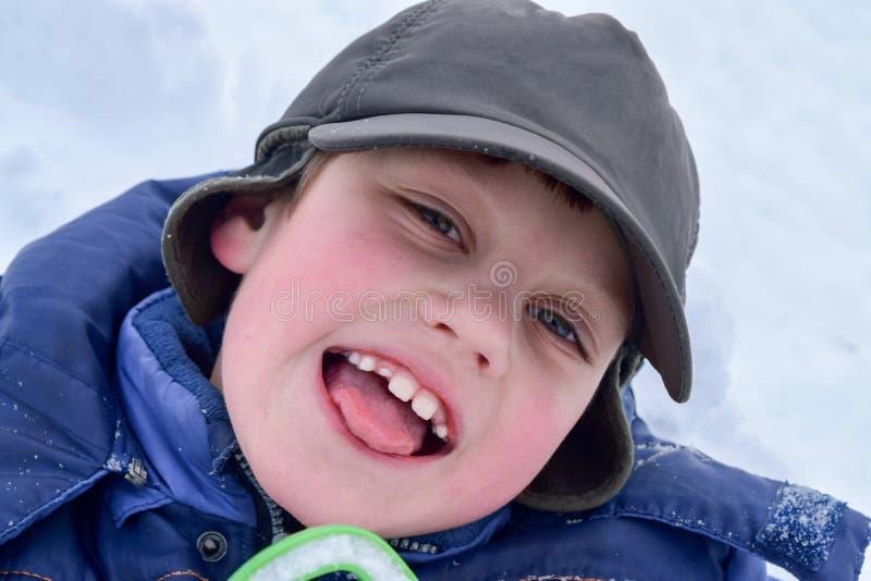 冬天帽子和夹克的一个快乐的男孩微笑并且调查照相机 免版税图库摄影