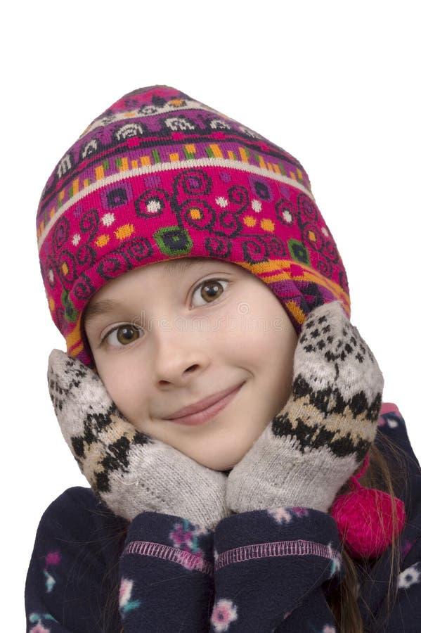 冬天帽子和手套的年轻摆在的女孩 免版税库存照片
