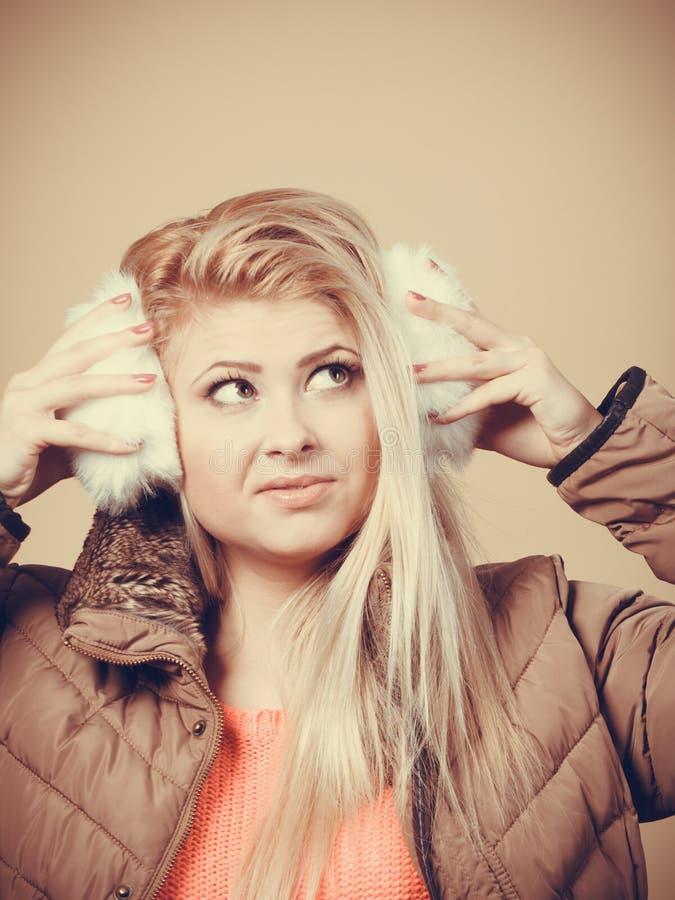 冬天御寒耳罩和夹克的白肤金发的妇女 免版税图库摄影