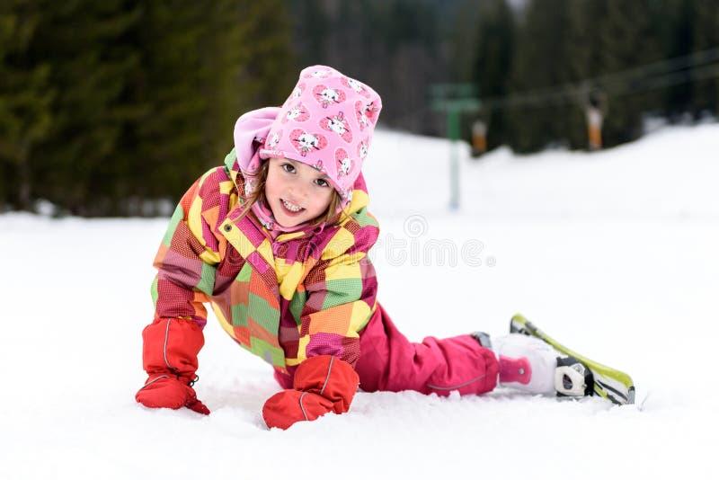 冬天成套装备的小女孩跌倒了,当滑雪时 免版税库存图片