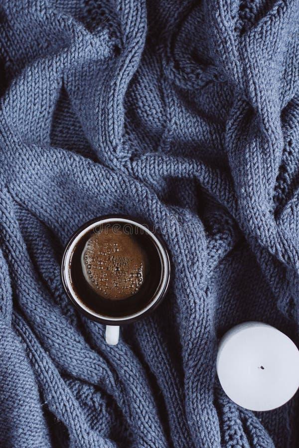 冬天或秋天舒适概念 咖啡和蜡烛在蓝色被编织的毛线衣 免版税库存图片