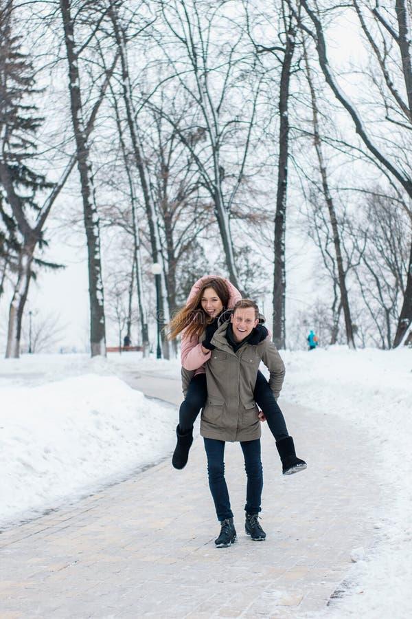 冬天旅客快乐的年轻夫妇  妇女在冬天多雪的公园乘坐一个人 库存图片