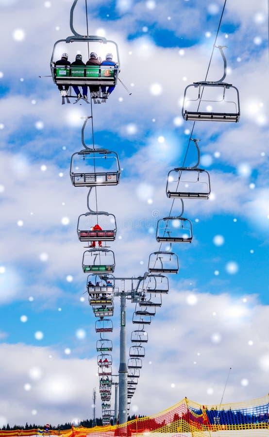 冬天旅游业在东欧 在蓝天背景的现代滑雪电缆车  滑雪胜地` Bukovel `,乌克兰 免版税库存照片