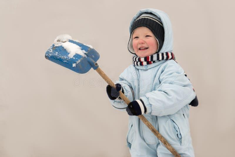 冬天时尚衣裳的一个愉快的孩子清洗雪与一把铁锹在他的村庄房子庭院里  家庭, traditio 免版税库存图片