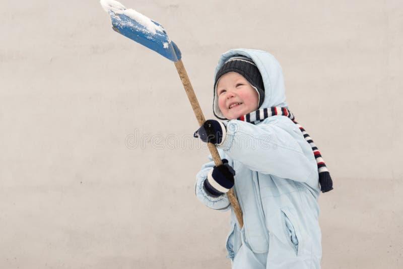 冬天时尚衣裳的一个愉快的孩子清洗雪与一把铁锹在他的村庄房子庭院里  家庭, traditio 库存照片