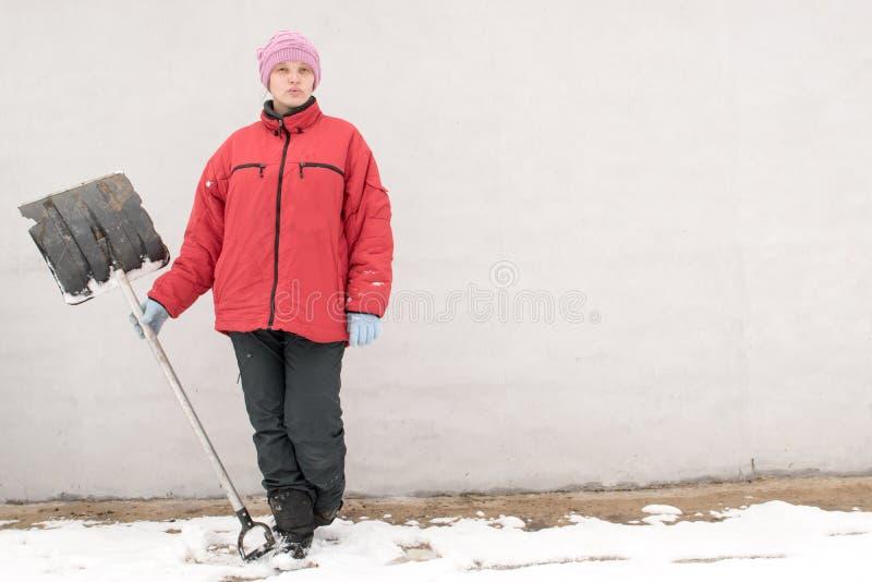 冬天时尚衣裳的美丽的女孩有铁锹的清除从雪的路 家庭,传统,假日 免版税库存图片