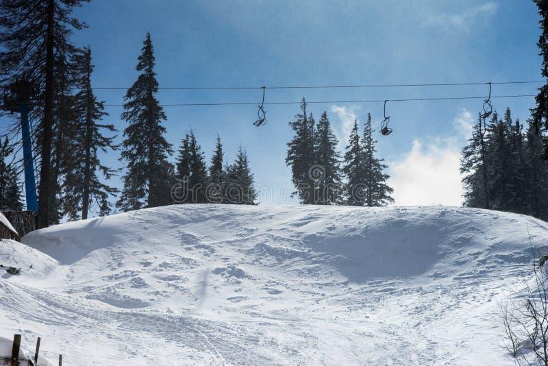 冬天有滑雪倾斜和滑雪吊车的山全景 免版税库存照片