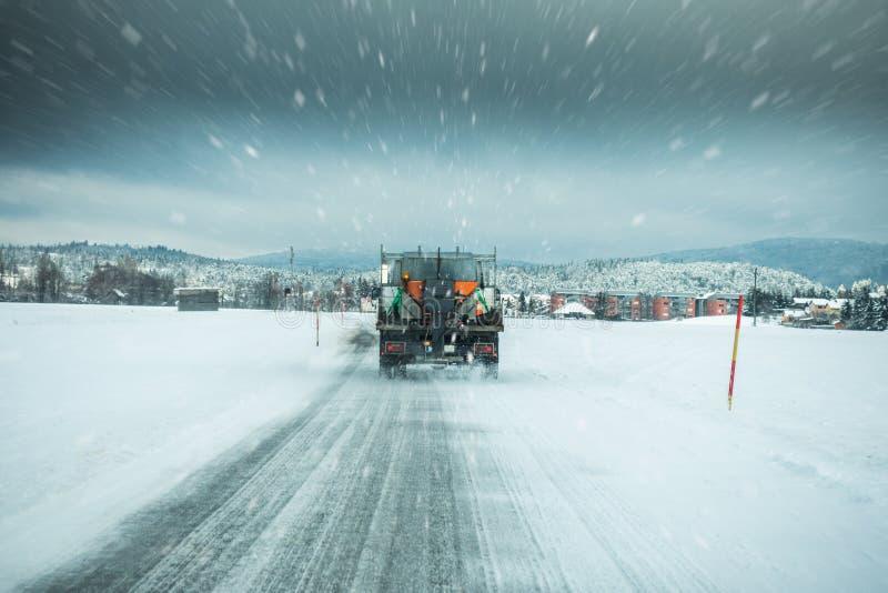 冬天服务卡车或铺砂机传播的盐防止的路面上冰在风雨如磐的雪冬日 库存图片