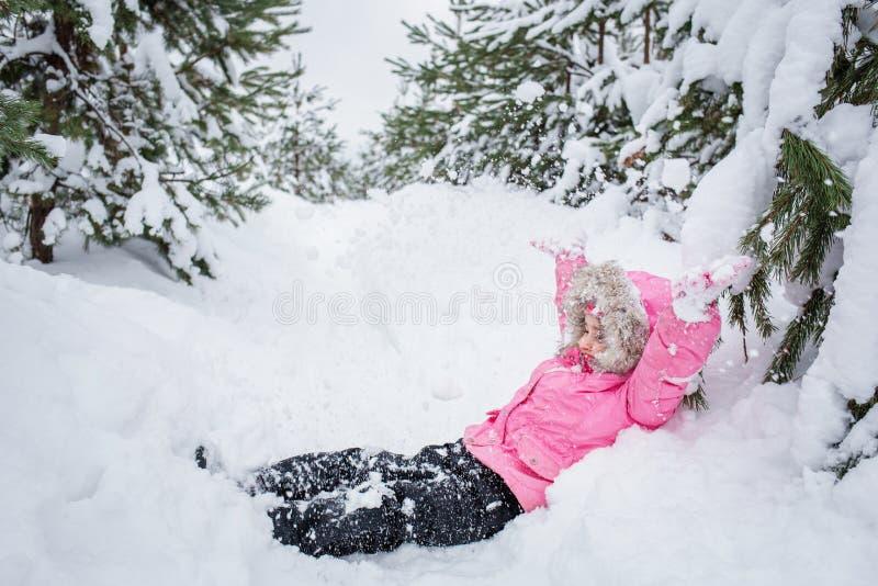 冬天杉木森林女婴的愉快的孩子一件桃红色夹克的投掷室外的雪 库存图片