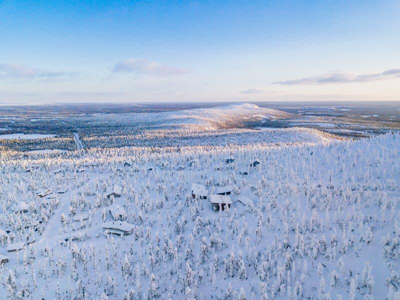 冬天森林鸟瞰图有冷淡的树、农村路和村庄的在芬兰 库存图片
