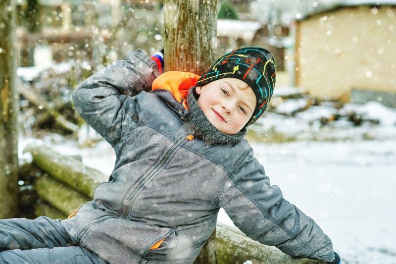 冬天步行的快乐的男孩,穿戴在夹克和帽子 免版税库存图片