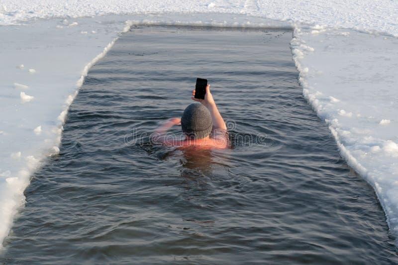 冬天游泳的恋人在一个坑的在冰照片himse 库存照片