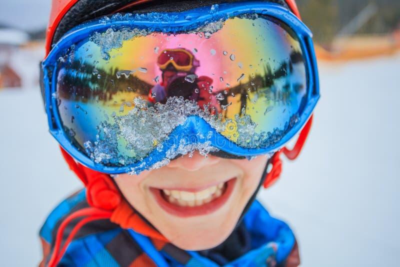 冬天滑雪场的逗人喜爱的滑雪者男孩 库存图片