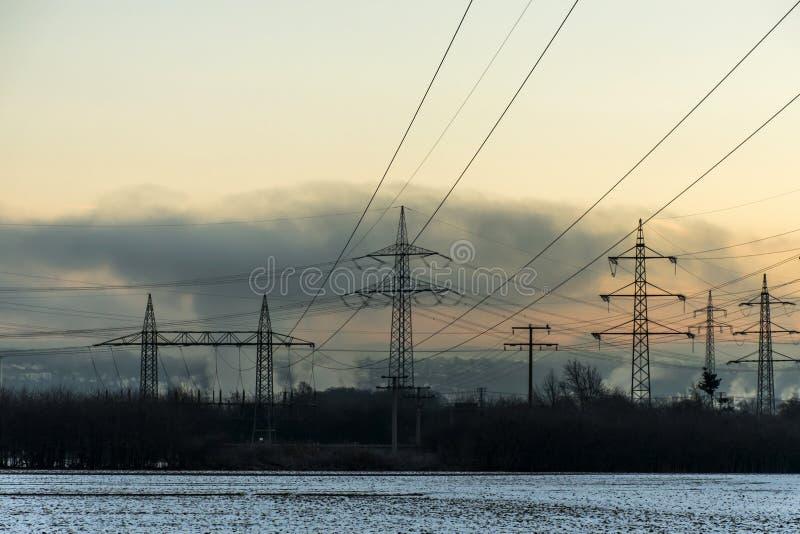 冬天电力塔风景雪白日落日出黎明 库存照片