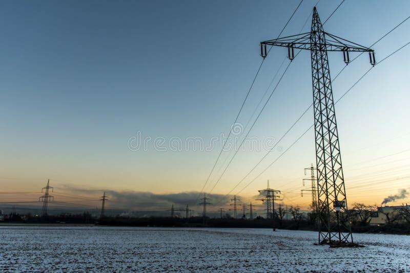 冬天电力塔风景雪白日落日出黎明 库存图片