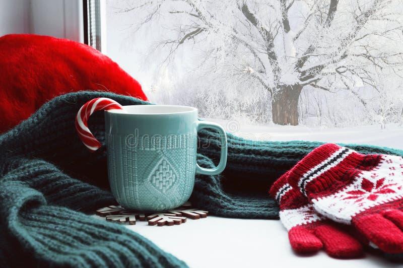 冬天背景-有棒棒糖、羊毛围巾和手套的杯子在户外窗台和冬天场面 图库摄影