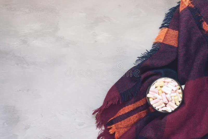 冬天舒适概念,横幅,大模型 咖啡用在白色上釉的杯子的蛋白软糖在灰色水泥的紫色温暖的羊毛围巾 库存照片