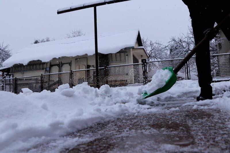 冬天获取力量 有塑料铁锹的一个人铲起从家车道的雪  仍然下雪和下雪 库存照片