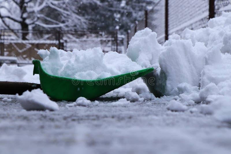 冬天获取力量 有塑料铁锹的一个人铲起从家车道的雪  仍然下雪和下雪 图库摄影