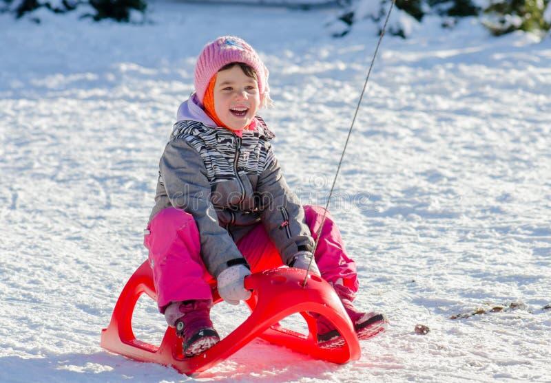 冬天衣服的小孩女孩在获得的雪橇乐趣 库存照片