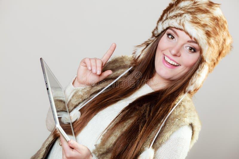 冬天衣物的妇女有片剂的 免版税库存照片