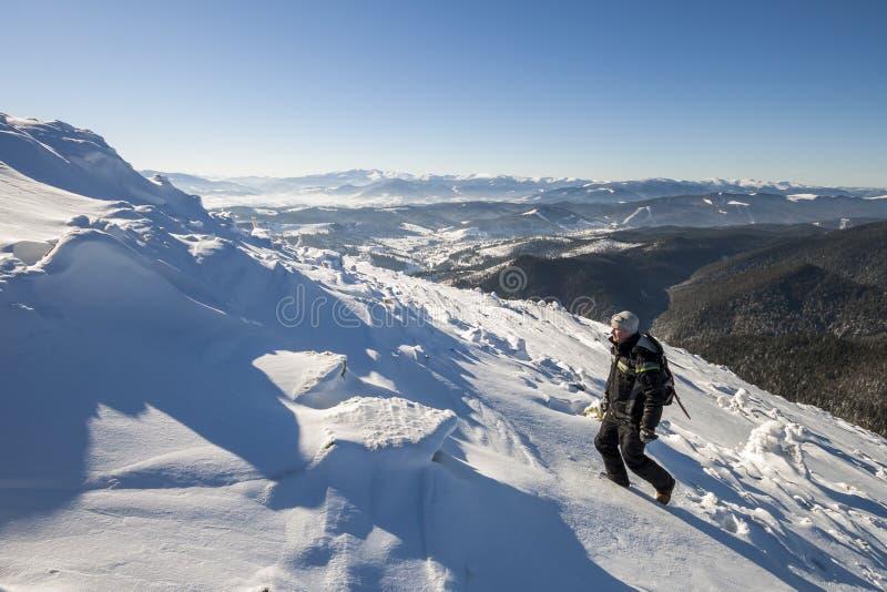 冬天衣物的旅游徒步旅行者登山人有背包上升的 图库摄影