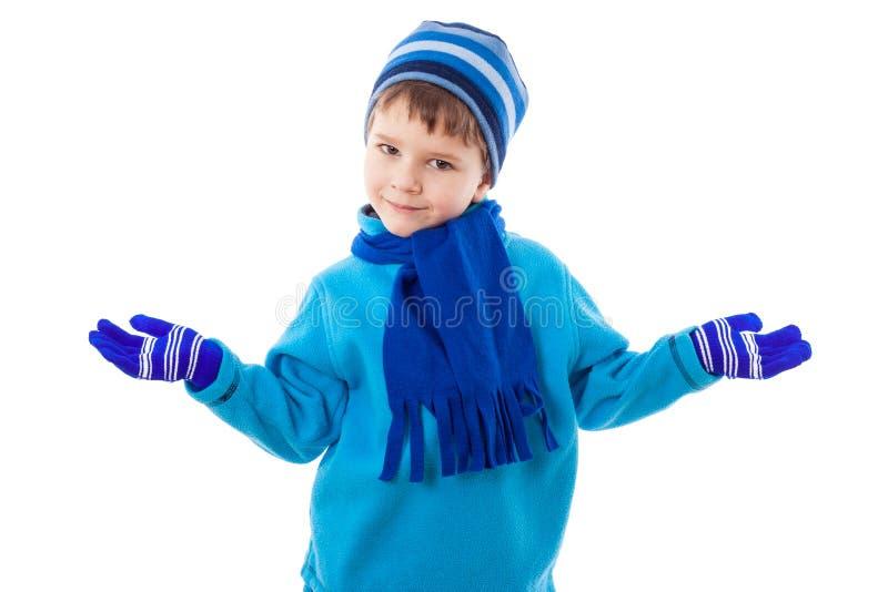 冬天衣裳的微笑的男孩投入了手对边 免版税库存照片