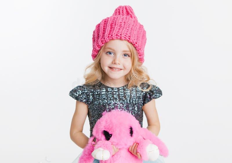 冬天衣裳 小卷曲女孩画象在白色隔绝的被编织的桃红色冬天帽子的 桃红色兔子玩具在她的手上 免版税库存照片