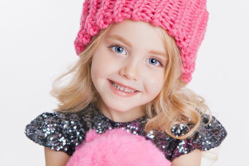 冬天衣裳 小卷曲女孩画象被编织的桃红色冬天帽子的 免版税库存照片