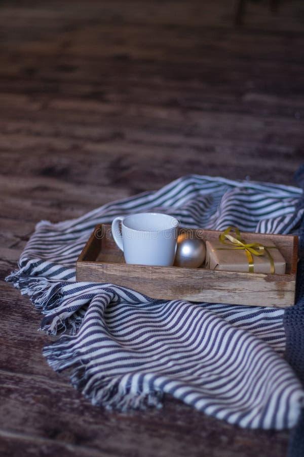冬天装饰:咖啡、礼物、盘子、球和舒适镶边格子花呢披肩 所选的重点 免版税库存照片