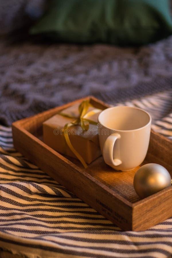 冬天装饰:咖啡、礼物、盘子、球和舒适镶边格子花呢披肩 所选的重点 免版税库存图片