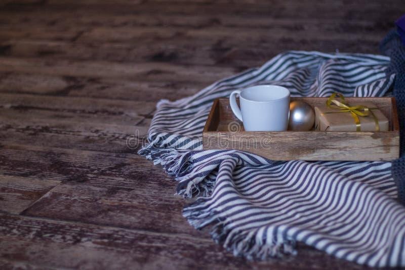 冬天装饰:咖啡、礼物、盘子、球和舒适镶边格子花呢披肩 库存图片