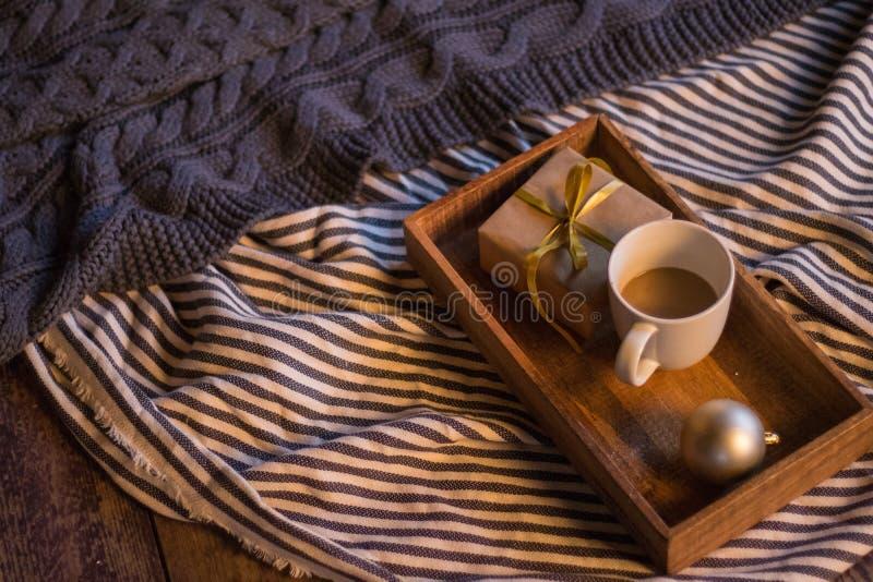 冬天装饰:咖啡、礼物、盘子、球和舒适镶边格子花呢披肩 库存照片