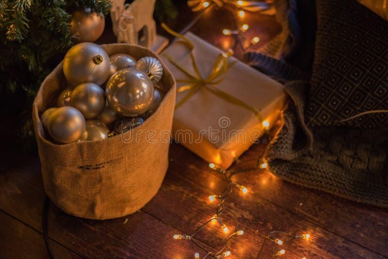 冬天装饰:圣诞树、礼物在工艺纸,木DIY鹿,诗歌选,金黄和白色球 所选的重点 免版税库存照片