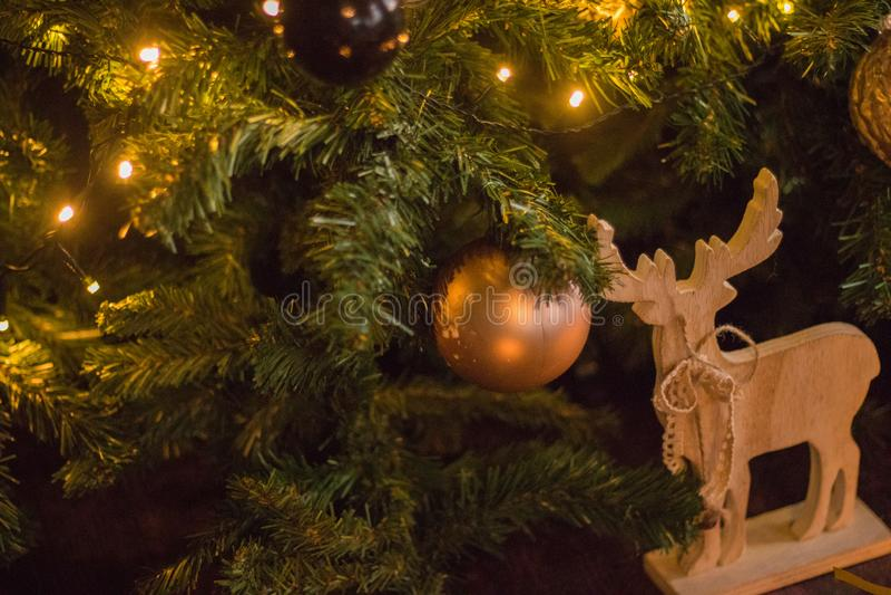 冬天装饰:圣诞树、礼物在工艺纸,木DIY鹿,诗歌选,金黄和白色球 所选的重点 库存图片