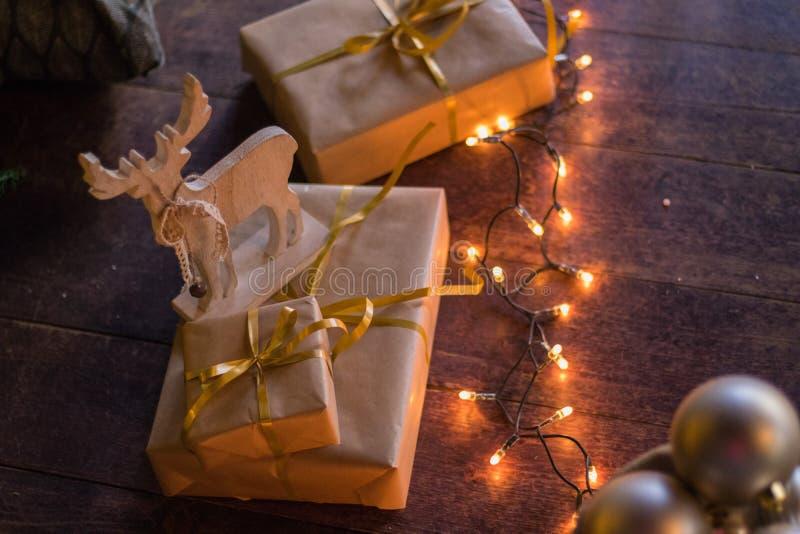 冬天装饰:圣诞树、礼物在工艺纸,木DIY鹿,诗歌选,金黄和白色球 所选的重点 库存照片