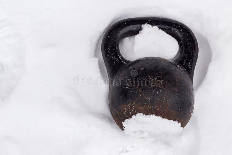 冬天训练街道锻炼的老生锈的kettlebell在雪 库存图片