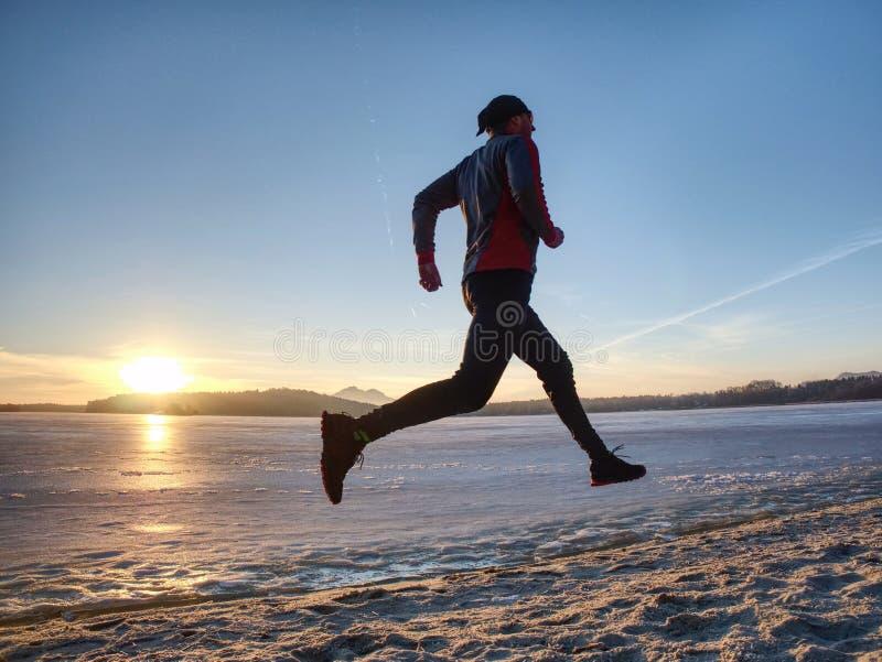 冬天训练 在冬天风景的赛跑者与天空蔚蓝 库存照片