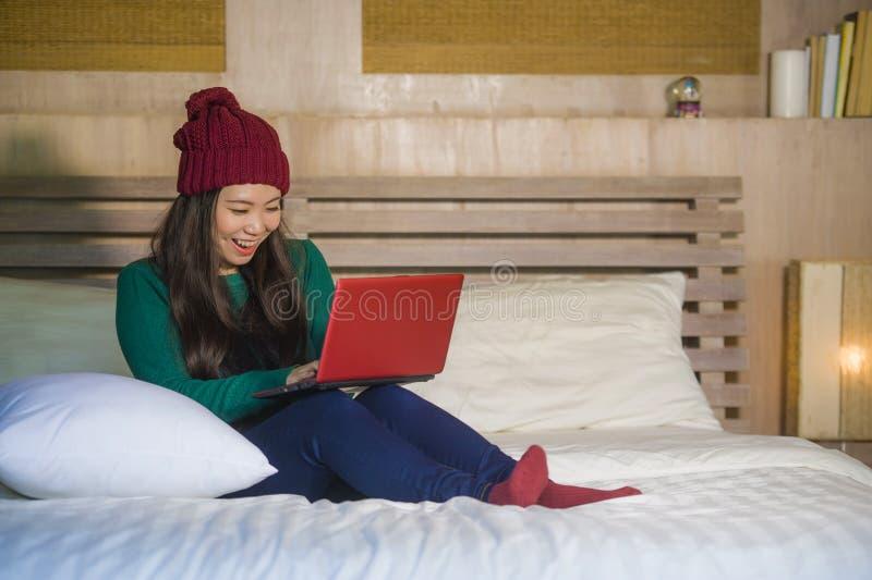 冬天象梁一样的开会的年轻美丽和愉快的亚裔中国女孩放松在床上使用手提电脑获得乐趣享用onli的 库存照片