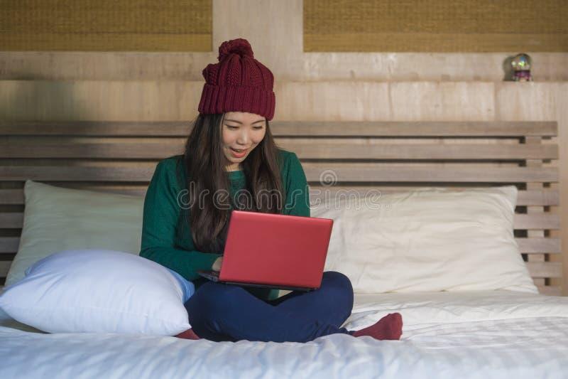 冬天象梁一样的开会的年轻美丽和愉快的亚裔中国女孩放松在床上使用手提电脑获得乐趣享用onli的 库存图片