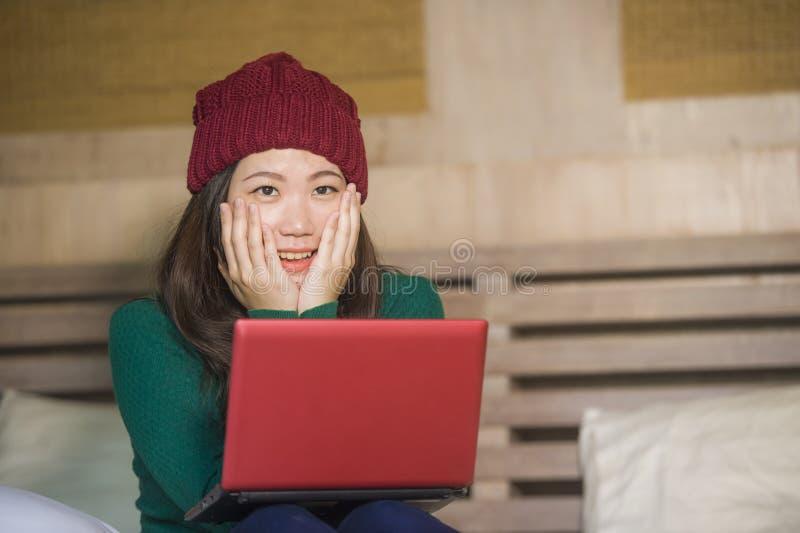 冬天象梁一样的开会的年轻美丽和愉快的亚裔中国女孩放松在床上使用手提电脑获得乐趣享用onli的 免版税库存照片
