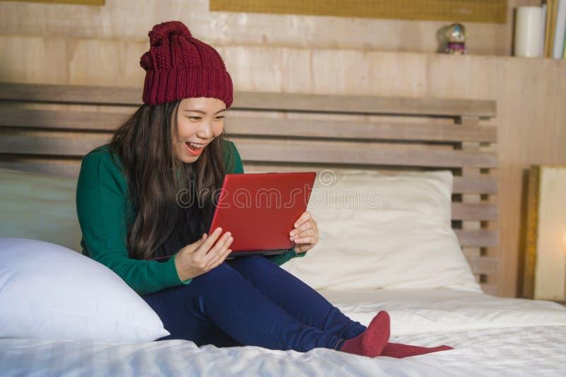 冬天象梁一样的开会的年轻美丽和愉快的亚裔日本女孩放松在床上使用手提电脑获得乐趣享受onl的 图库摄影