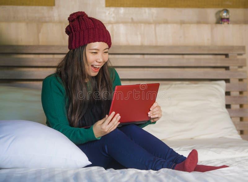 冬天象梁一样的开会的年轻美丽和愉快的亚裔韩国女孩放松在床上使用手提电脑获得乐趣享用onlin的 免版税库存图片