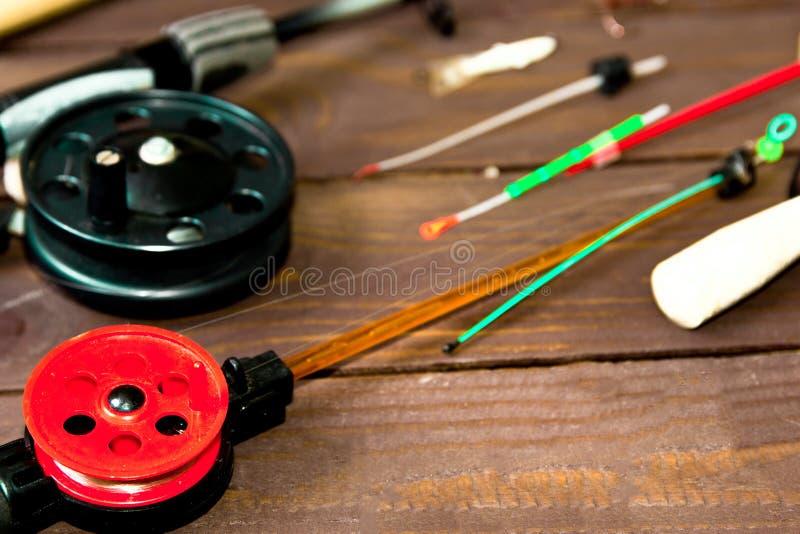 冬天钓鱼的滑车 钓鱼竿和辅助部件在一张木桌上 r 免版税图库摄影