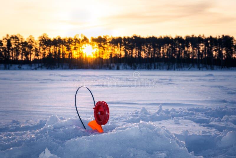 冬天钓鱼的钓鱼竿在黎明 免版税图库摄影