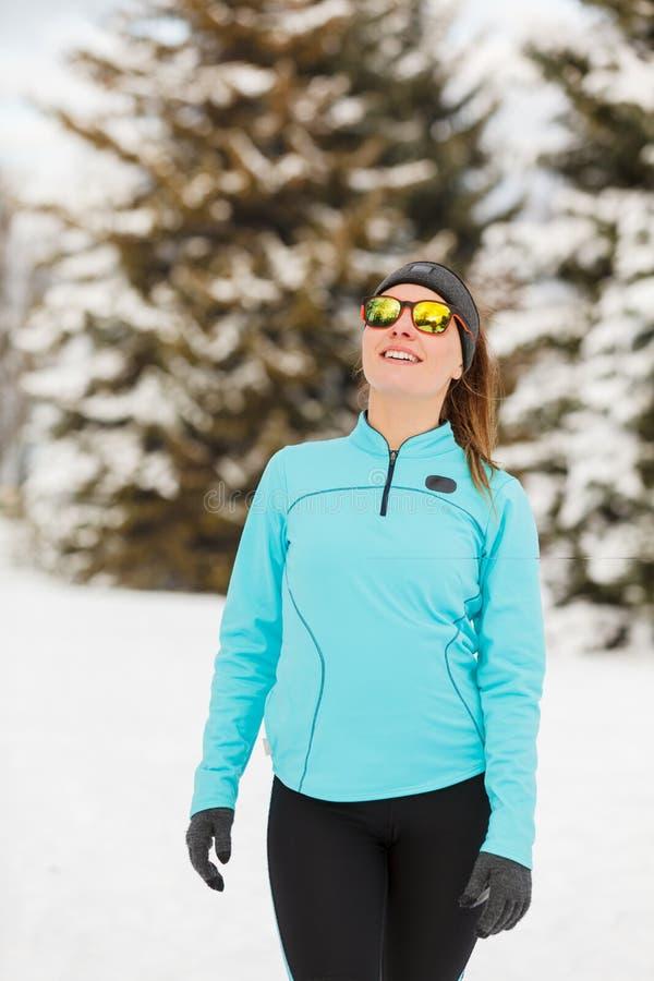 冬天锻炼 女孩佩带的运动服和太阳镜 免版税库存照片