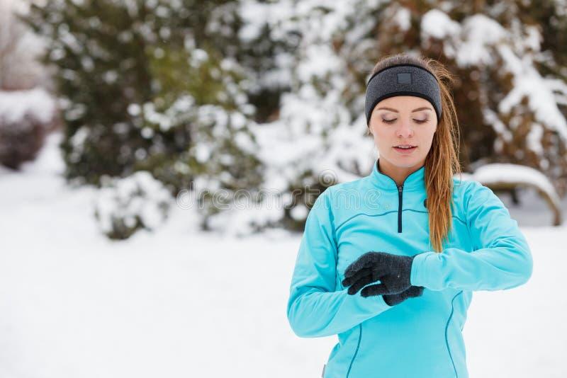 冬天锻炼 女孩佩带的运动服,看手表 免版税库存图片