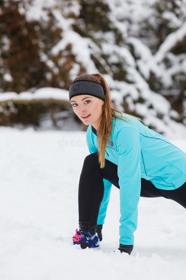 冬天锻炼 女孩佩带的运动服,舒展锻炼 免版税库存图片