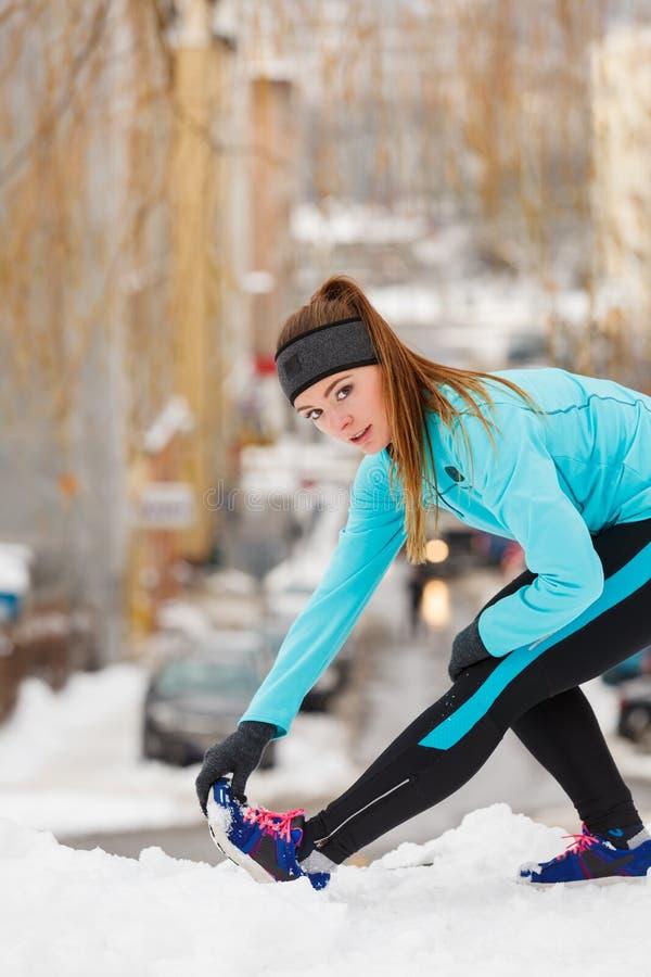 冬天锻炼 女孩佩带的运动服,舒展锻炼 免版税库存照片